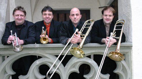 Vier Musiker mit Instrumenten am Geländer.