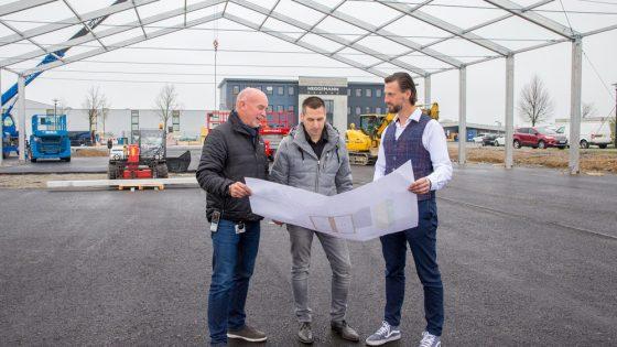 Drei Männer stehen in einer Halle und schauen auf einen Bauplan.