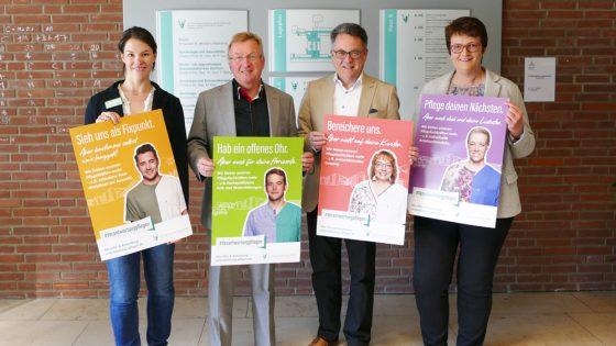 Vier Personen halten Plakate.