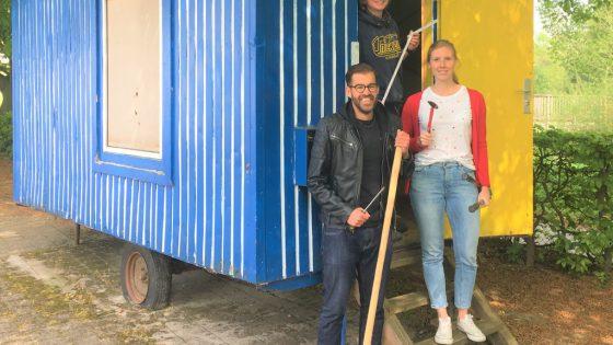 Drei Personen vor einem Bauwagen.