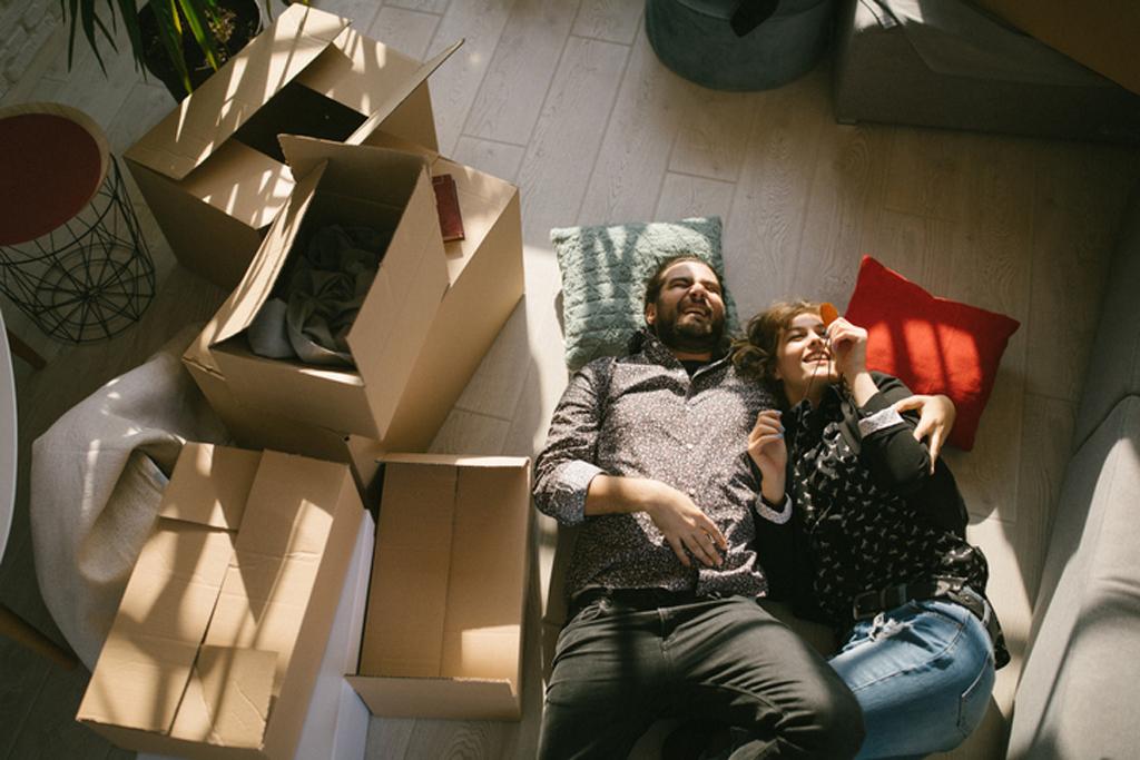 Paar liegt auf dem Boden zwischen Umzugskartons.