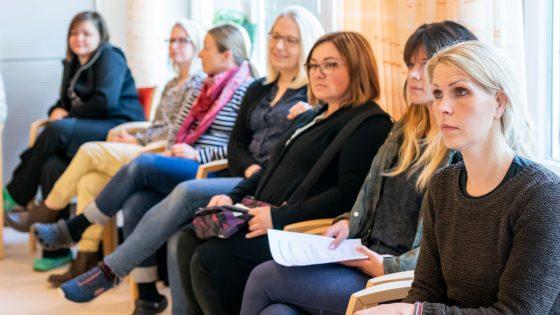 Frauen in einer Reihe sitzend.