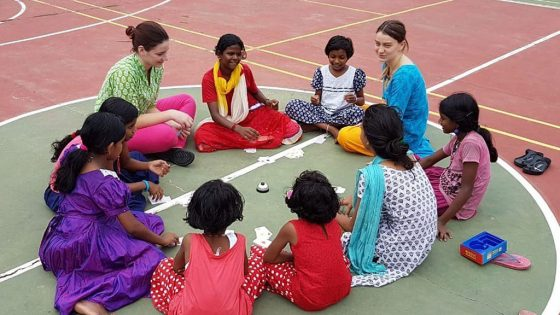 Zwei erwachsene Frauen sitzen mit Kindern im Kreis.