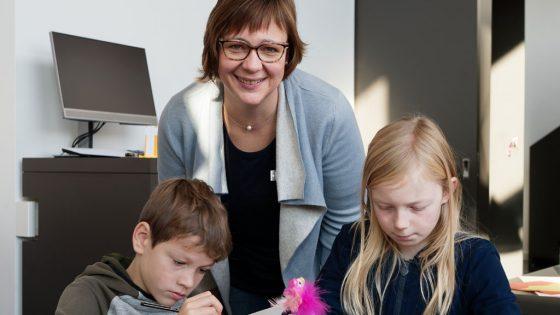Im Vordergrund zwei Kinder sitzend, im Hintergrund eine Erwachsene Frau.