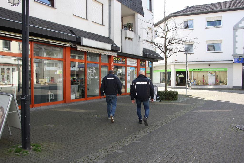 Zwei männer vom ordnungsamt gehen durch leere Straßen.