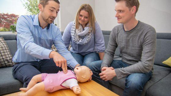 Jan-Niklas erläutert Julia und Daniel am Baby-Übungsmodell wichtige Handgriffe.