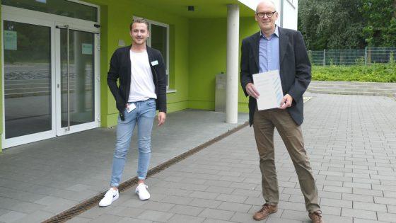 Zwei Männer stehen vor Gebäude, Einer mit Zertifikat in der Hand.