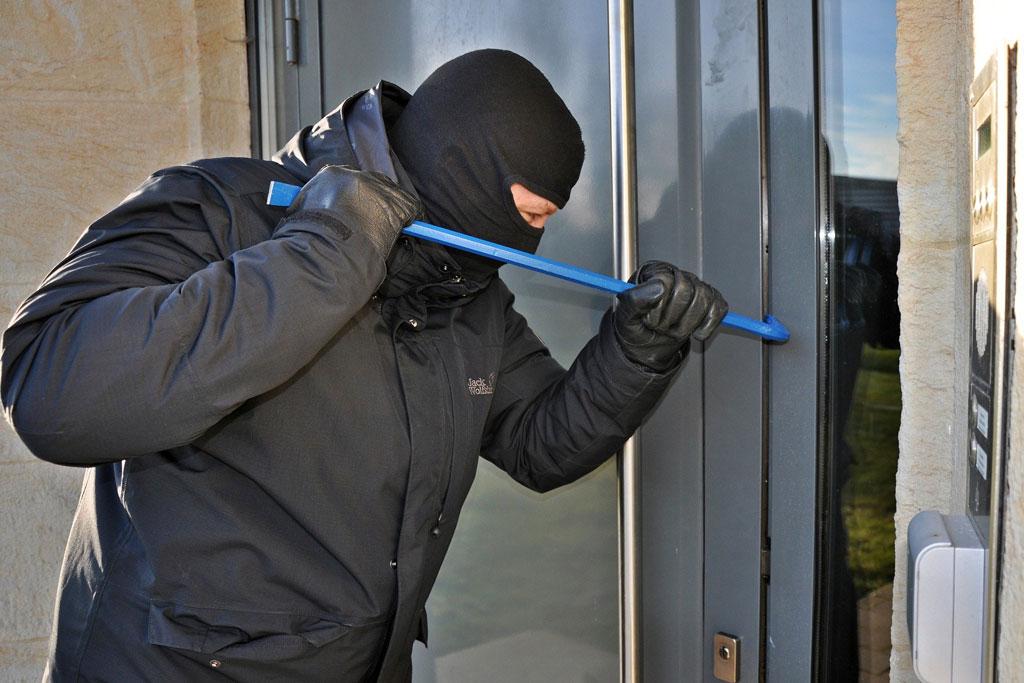 Einbrecher bearbeitet eine Haustür mit Brechstange.
