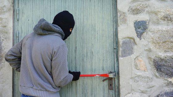Einbrecher mit Kaputze und Brechstange an einer Tür